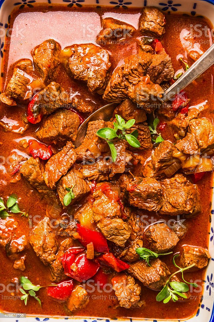 Beef braised in tomato paprika sauce with spoon, close up stock photo