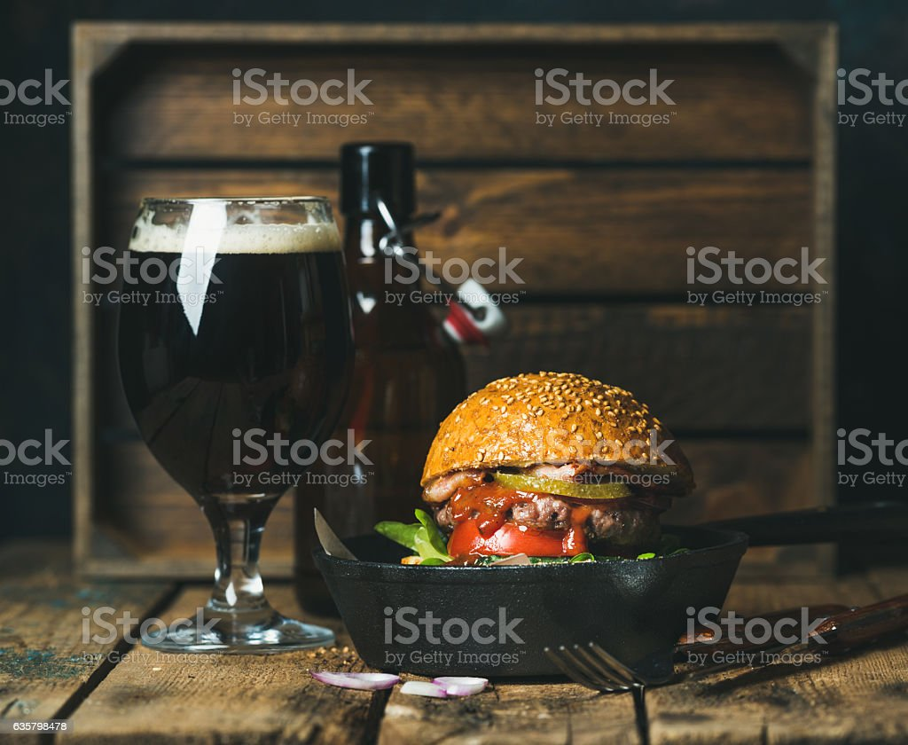 Beef burger with crispy bacon, fresh vegetables and dark beer stock photo