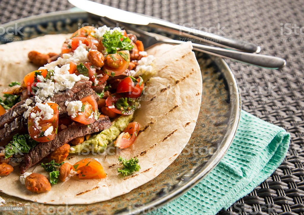 Beef Buritto with chilli lime greens & feta stock photo