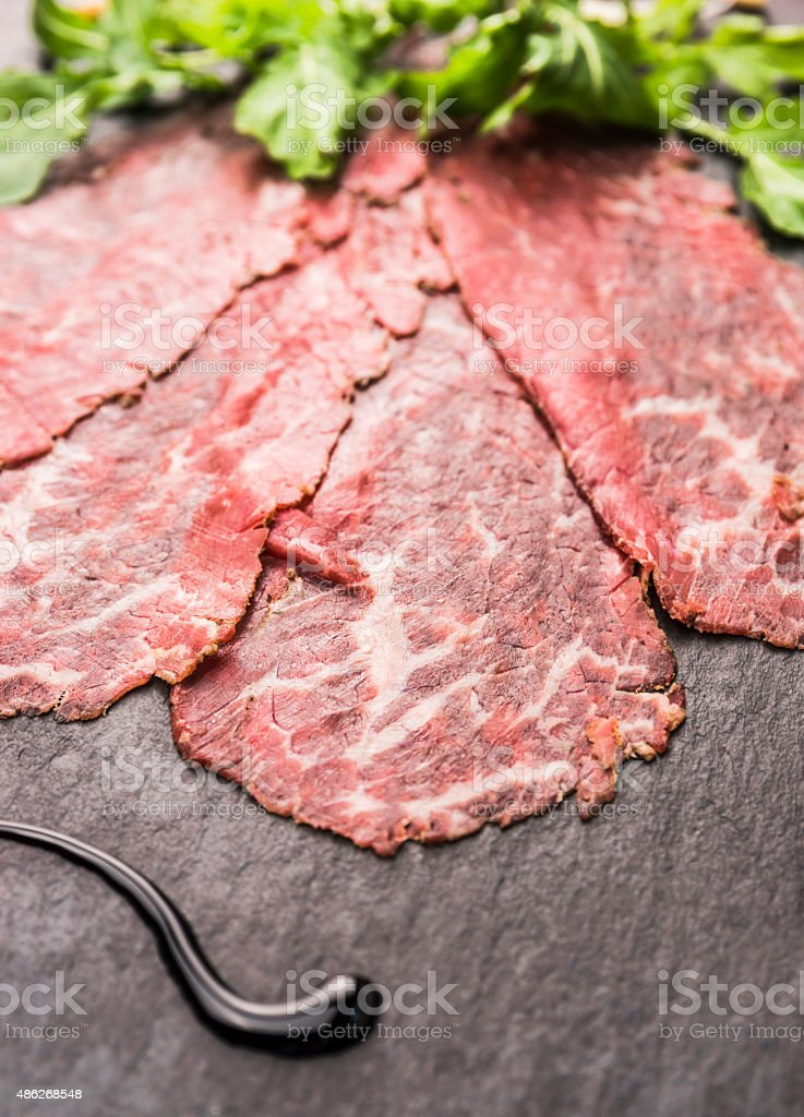 Beef Carpaccio with balsamic on slate background stock photo