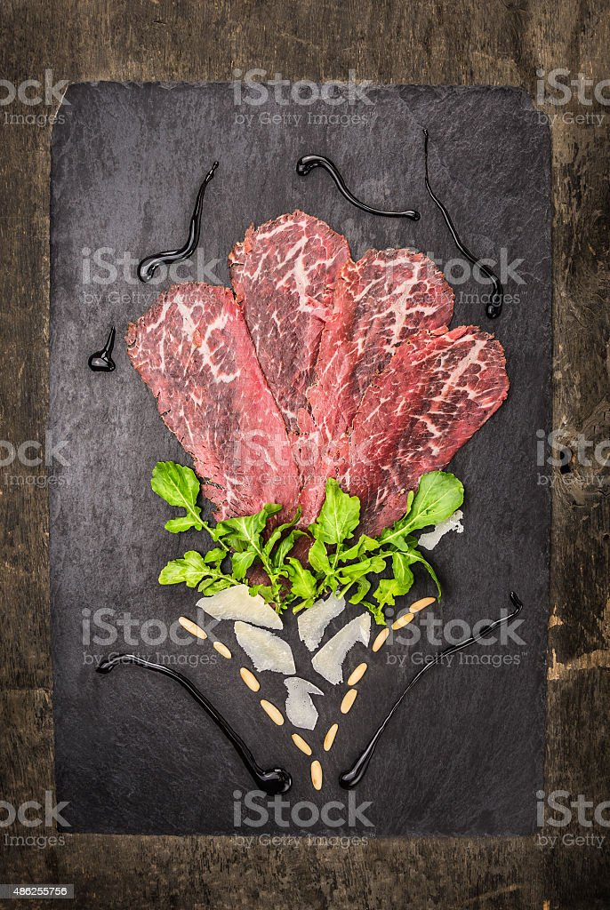 Beef carpaccio with parmesan, arugula, pine nuts and balsamic stock photo
