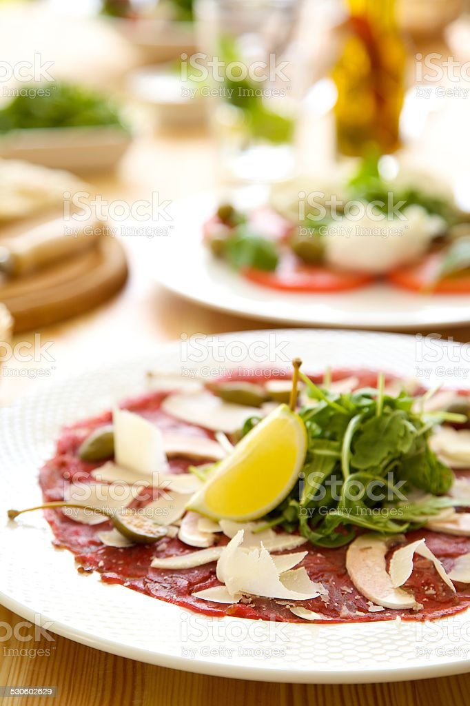 beef carpaccio with parmesan, capers and rucola stock photo