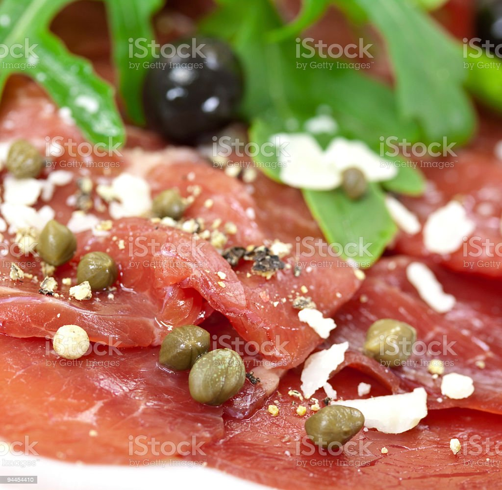 Beef carpaccio with pepper, rucola and parmesan stock photo