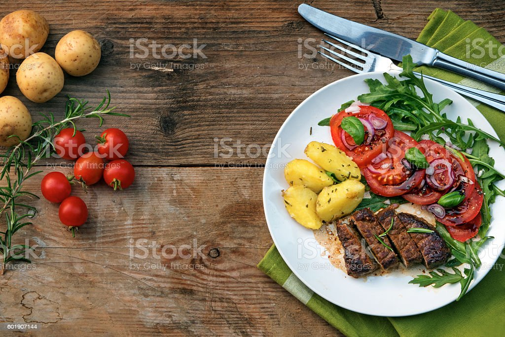 beef filet with potatoes and salad on wood from above stock photo