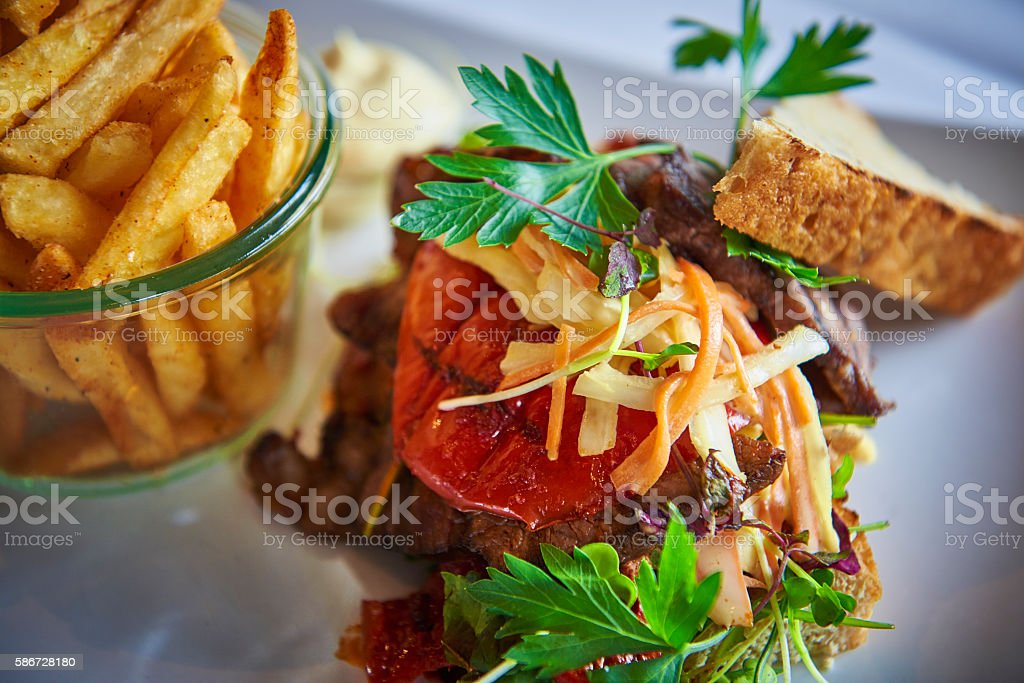 Beef garnished with green herbs and french fries stock photo