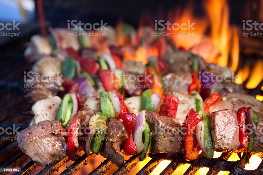 Beef Kebabs on a Fiery Grill with Flames stock photo