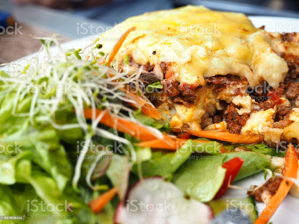 Beef lasagna served with fresh salad. stock photo