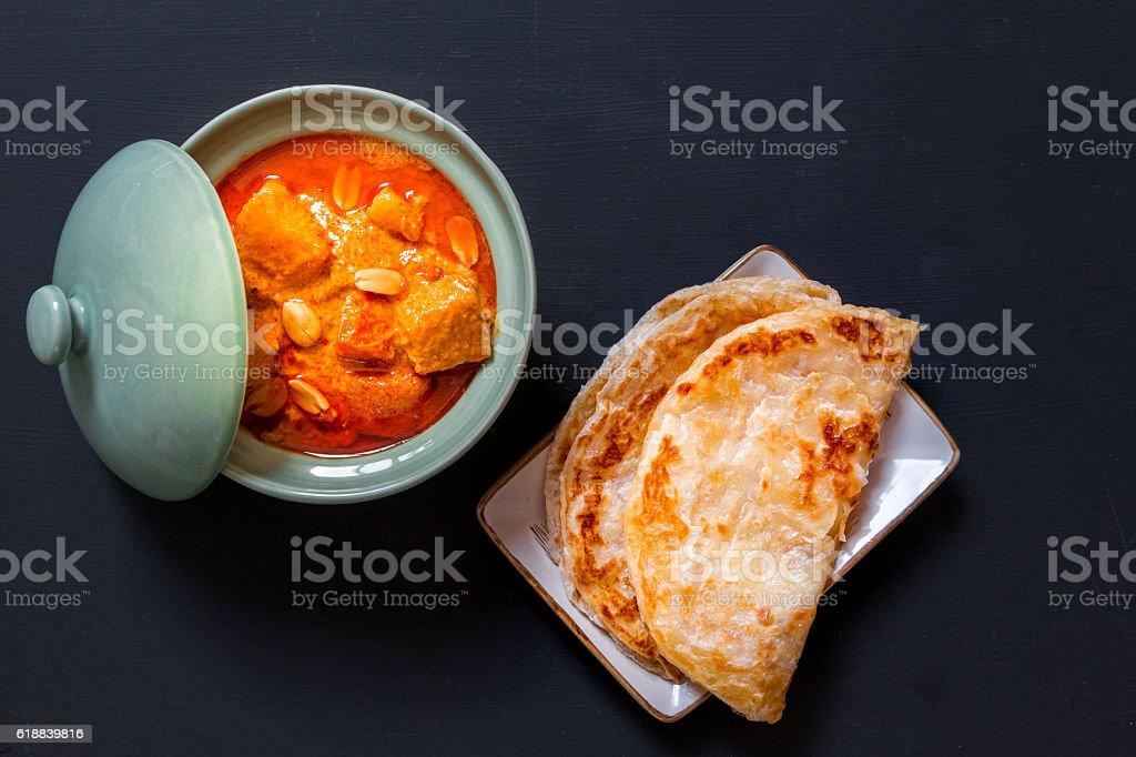 Beef massaman curry, thai cuisine eat with roti on black stock photo