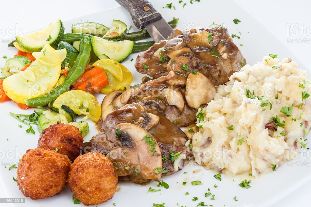 Beef medallions served with mushroom sauce and vegetables. stock photo