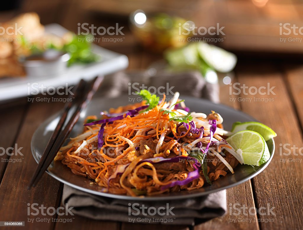 beef pad thai stir fry dish on plate with chopsticks stock photo