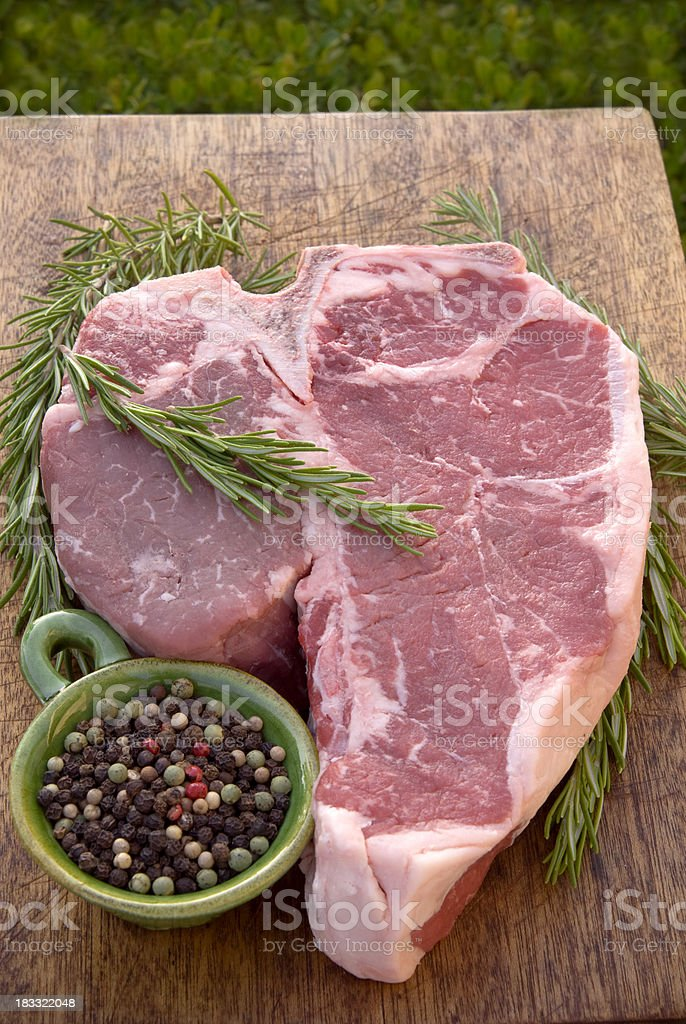 Beef Porterhouse T-Bone Raw Meat Steak Cooking Dinner: Rosemary & Pepper royalty-free stock photo