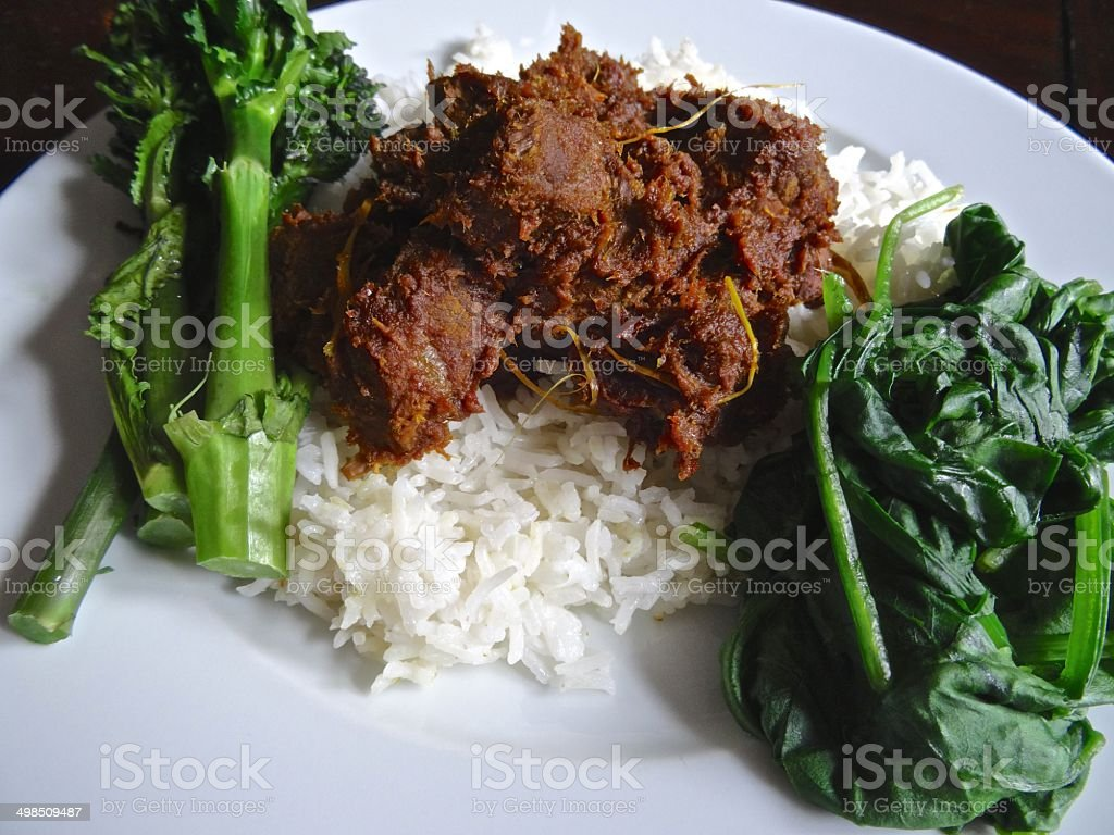 Beef, rendang curry with rice, broccoli and spinach royalty-free stock photo