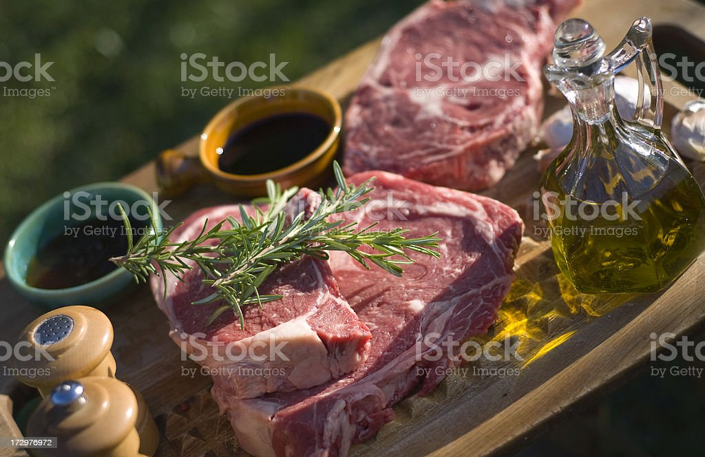 Beef Rib Eye Steaks, Raw Meat & Rosemary Marinade Barbeque Cooking royalty-free stock photo