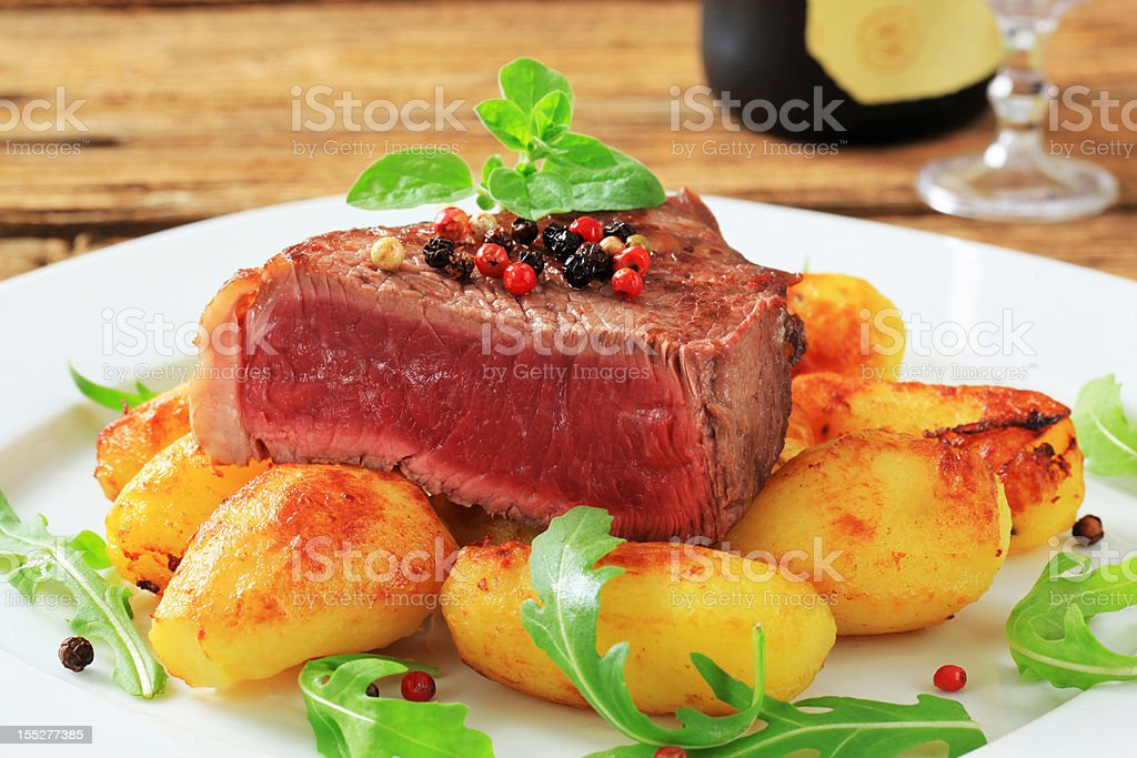 Beef steak and roasted potatoes royalty-free stock photo