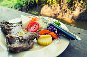 Beef steak and salad on table.