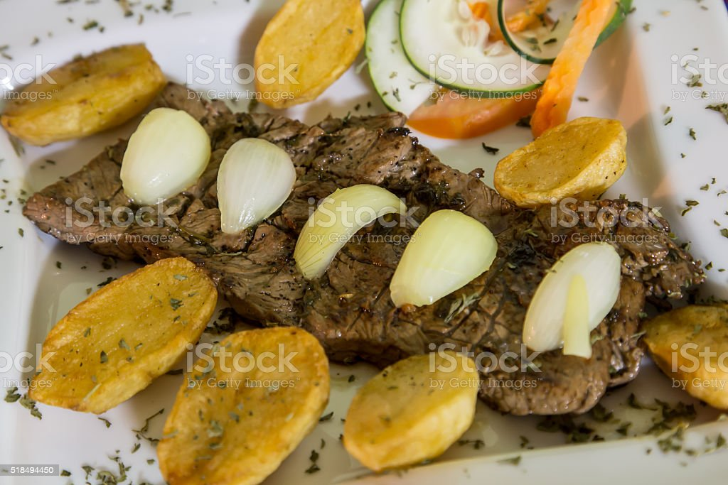 beef steak cooked with onion and platan stock photo