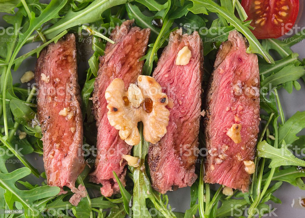 beef steak medium on Roccola leaves with walnuts stock photo