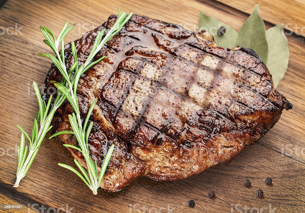 Beef steak on a wooden table. stock photo