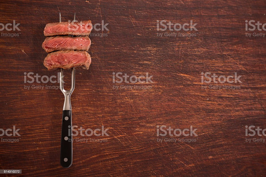Beef steak on fork stock photo