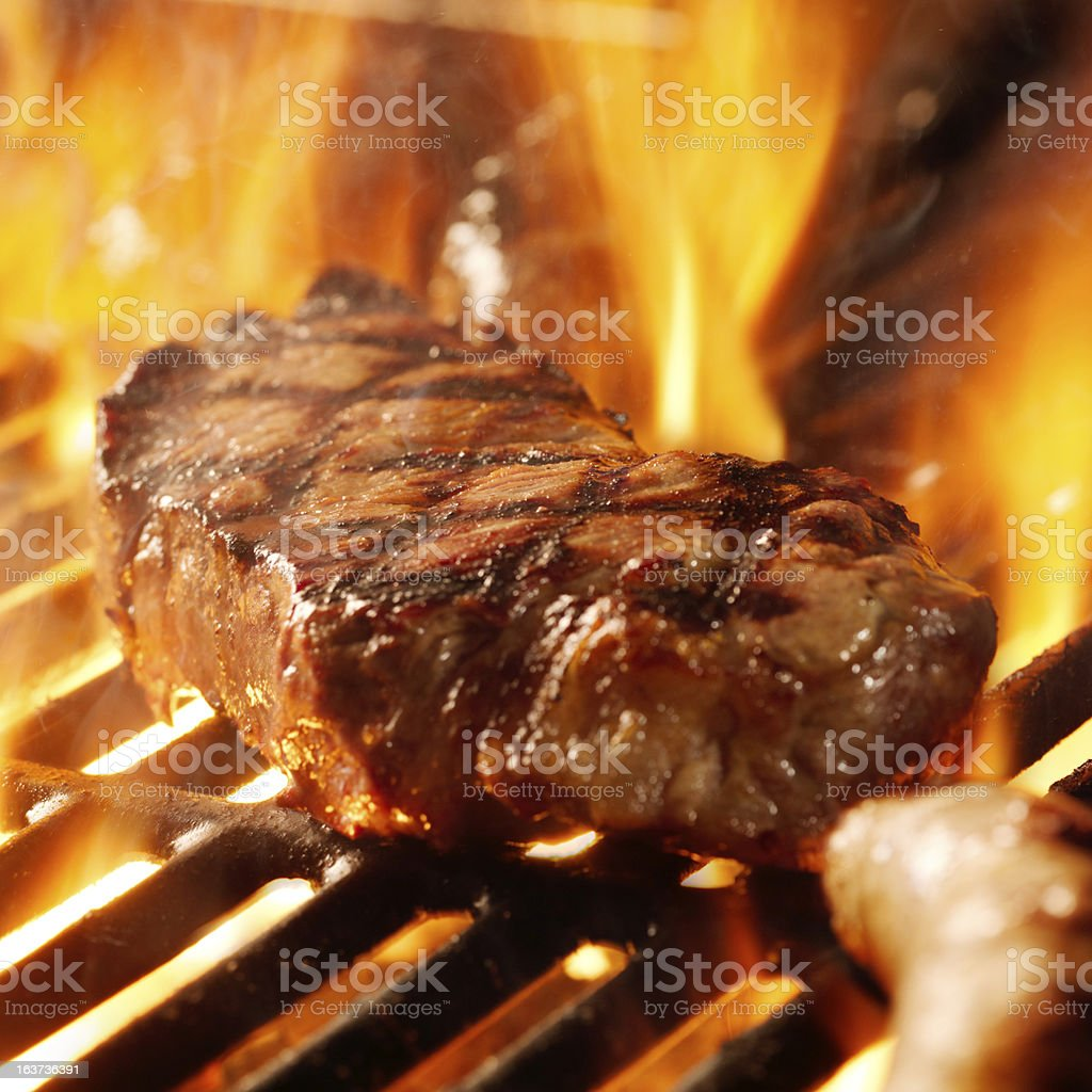 beef steak on the grill with flames stock photo