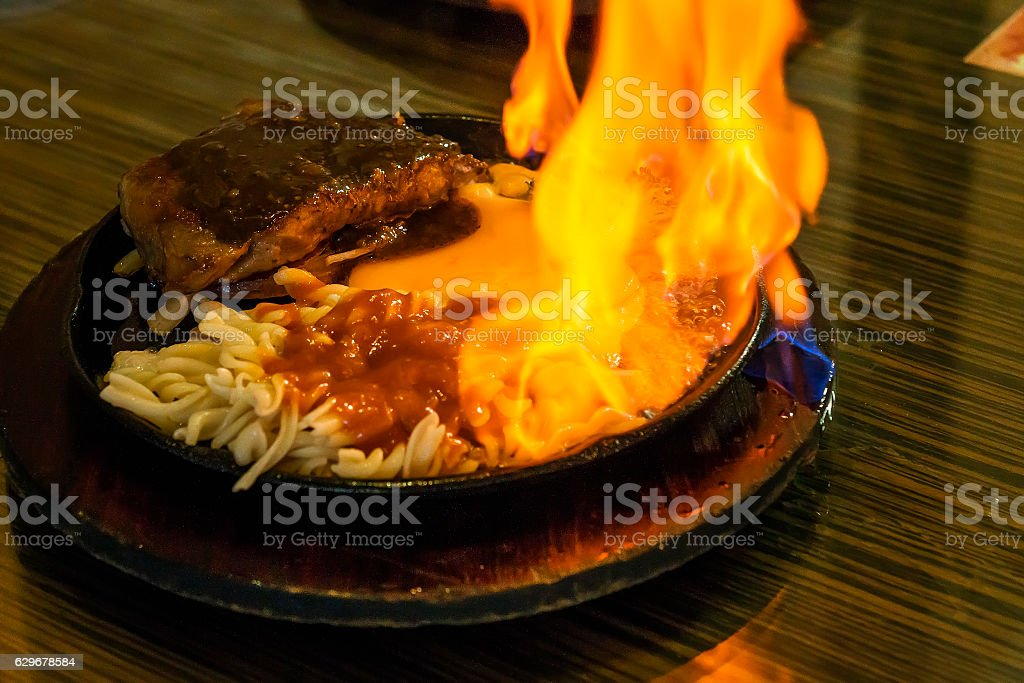 beef steak on the grill with flames. stock photo