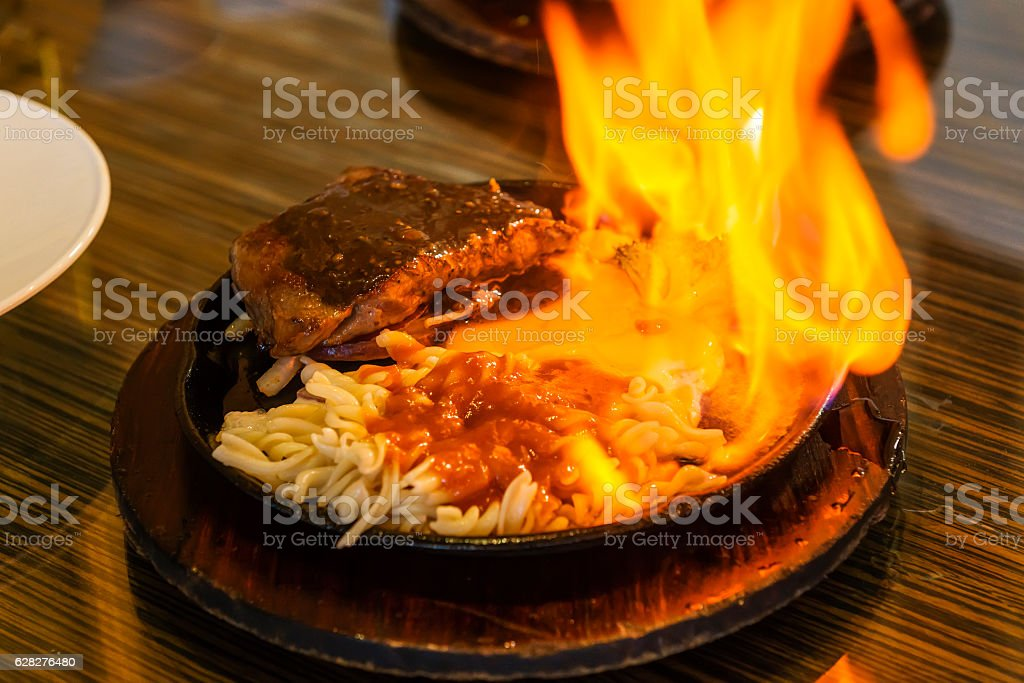 beef steak on the iron plate with flames. stock photo