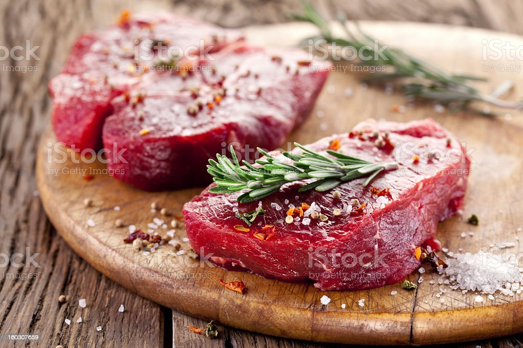 Beef steak seasoned with hot pepper, salt and rosemary royalty-free stock photo