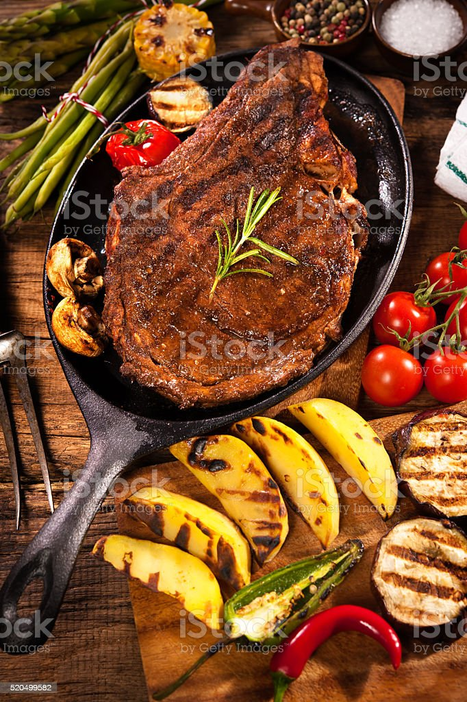 Beef steak with grilled vegetables on wood stock photo