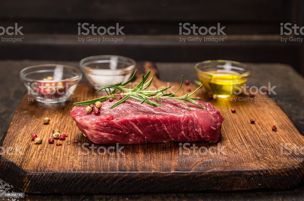 Beef steak with ingredients cooking - rosemary,oil, and spices stock photo
