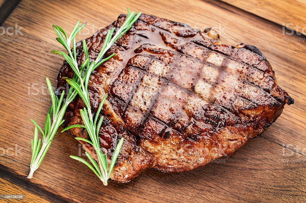 Beef steak with rosemary on a wooden table. stock photo