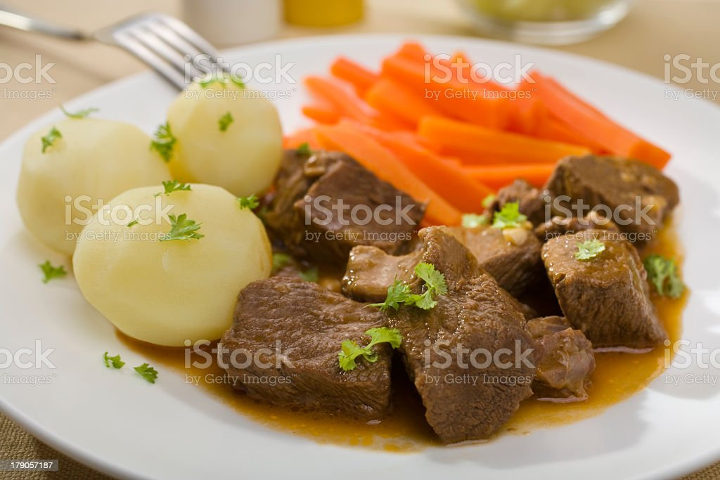 Beef stew with potatoes and carrots on a white plate stock photo