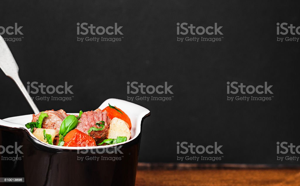 Beef stew  with vegetables in black pot . Selective focus. stock photo