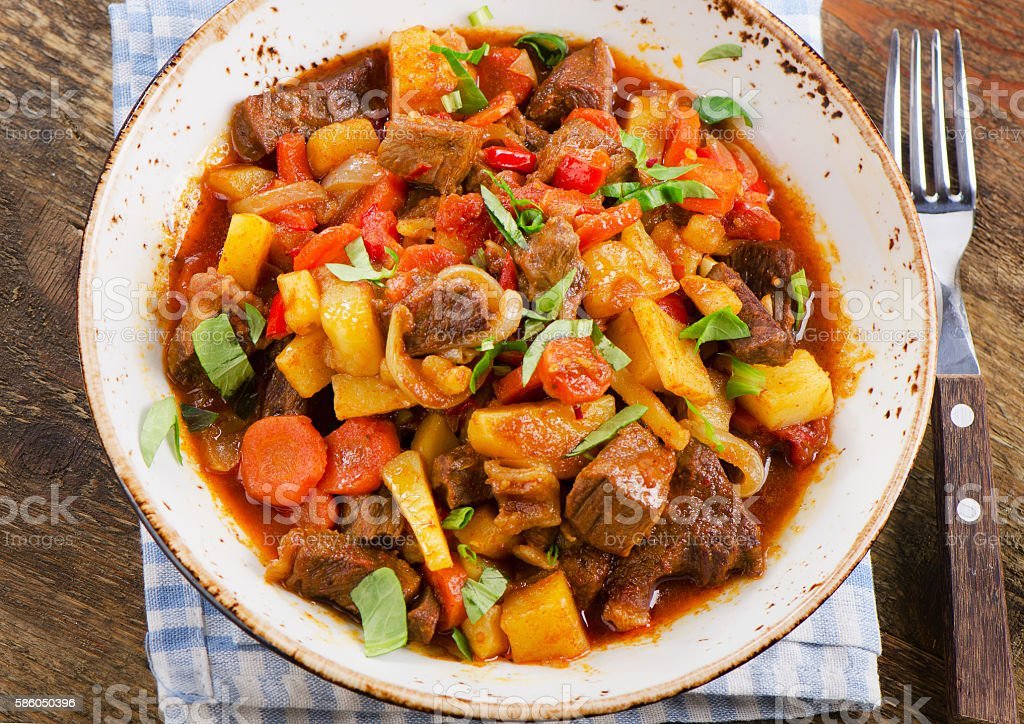 Beef stew with vegetables on a rustic wooden table. stock photo