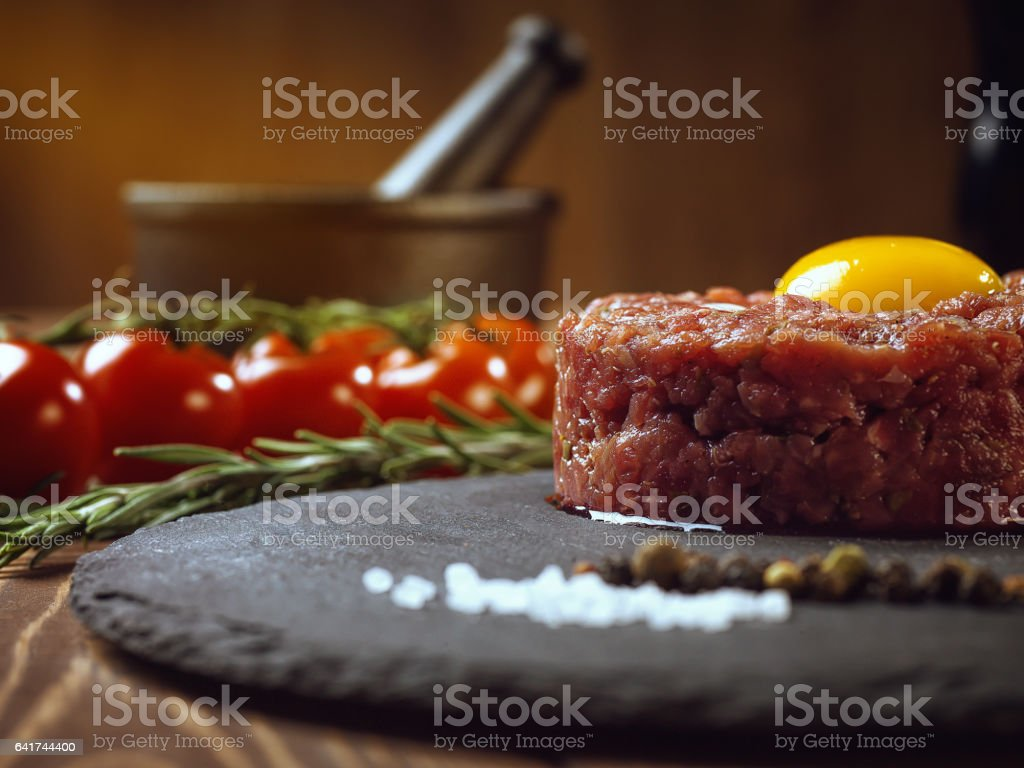 Beef tartar with an egg on a stone plate. stock photo