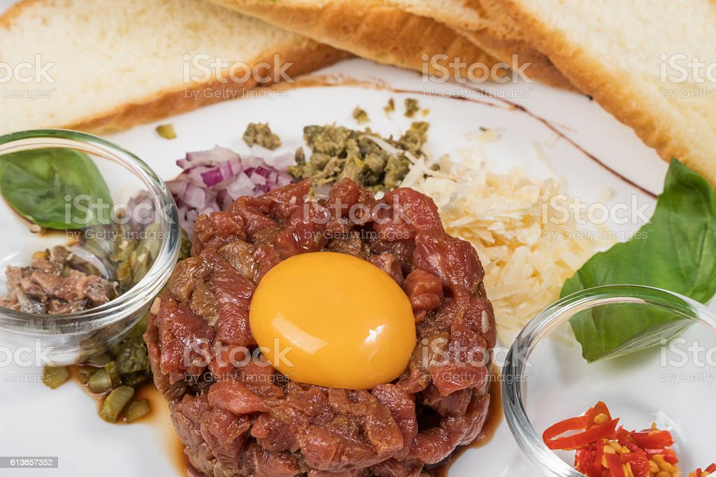 Beef tartare with egg and bread stock photo