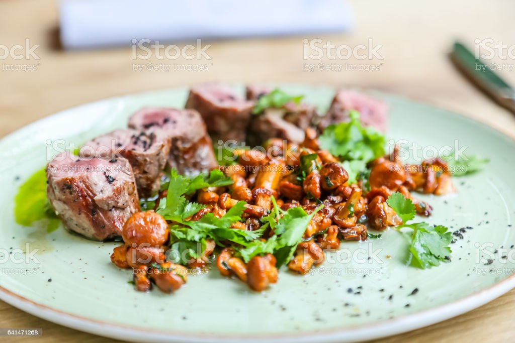 Beef tenderloin with fried chanterelles lying on a plate. stock photo