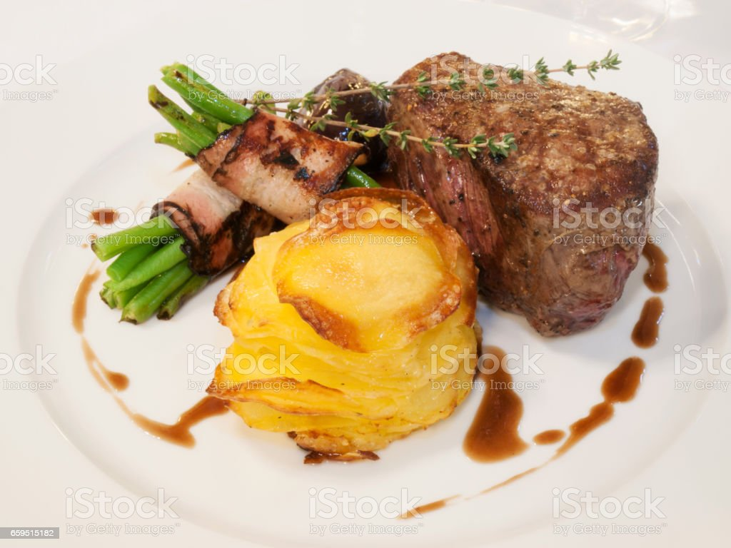 Beefsteak with beans in bacon stock photo