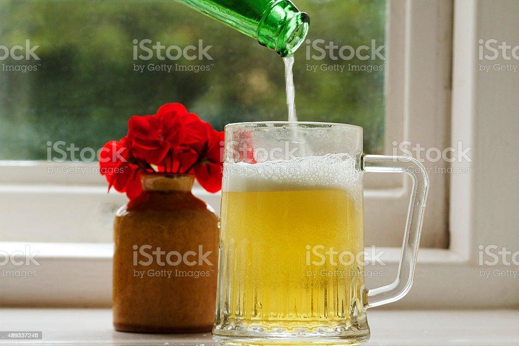 Birra è versato in un bicchiere foto stock royalty-free
