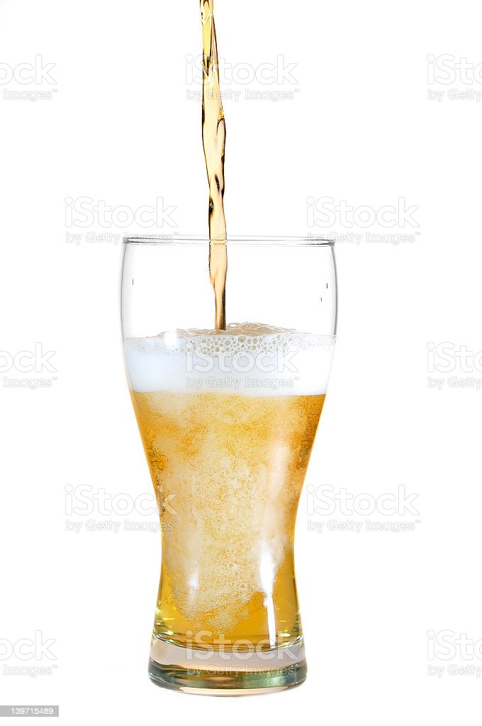 Beer being poured into a pint glass from above stock photo