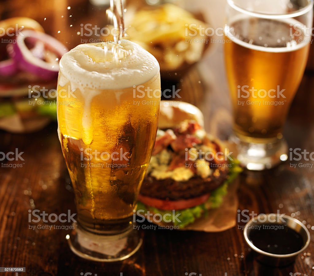 beer being poured into glass with gourmet hamburgers stock photo
