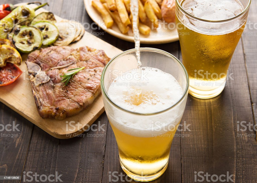 Beer being poured into glass with steak and french fries stock photo