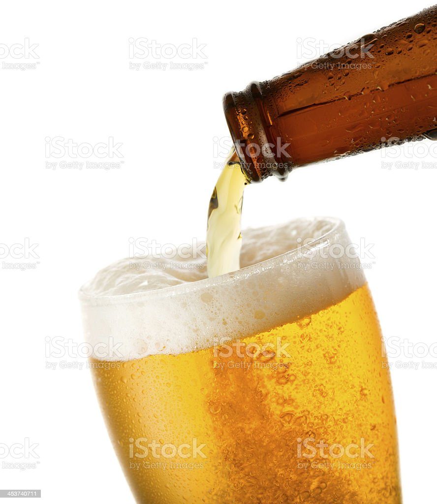 Beer being poured to the brim into a glass stock photo