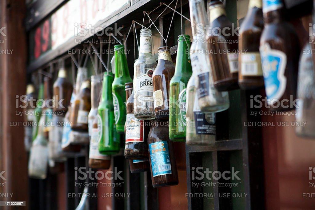 beer bottles hung outside of a bar stock photo