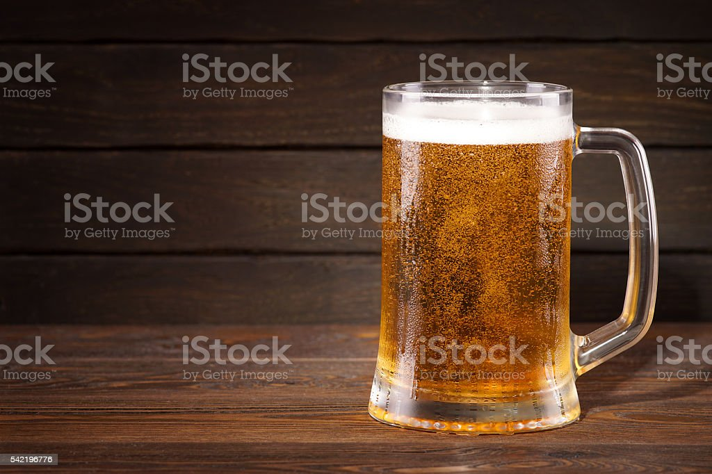 Beer. Cold beer in wineglass on a dark background. stock photo