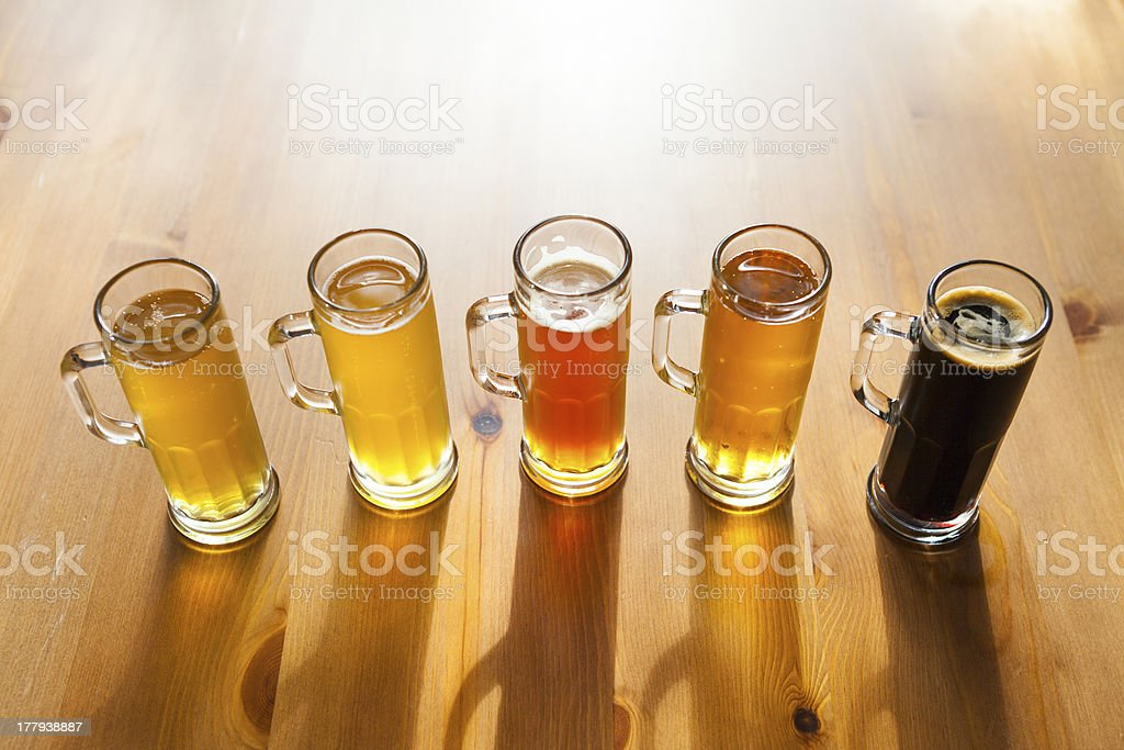 A beer flight in mini beer mugs on a wooden surface royalty-free stock photo