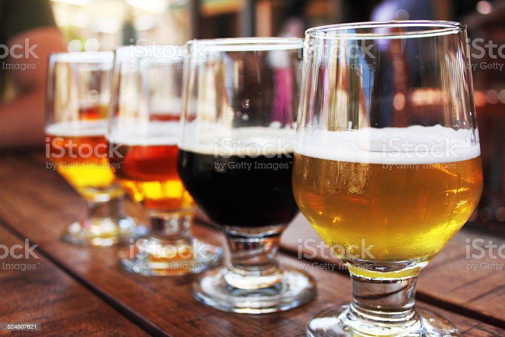 Beer Flight of four beers in glasses stock photo