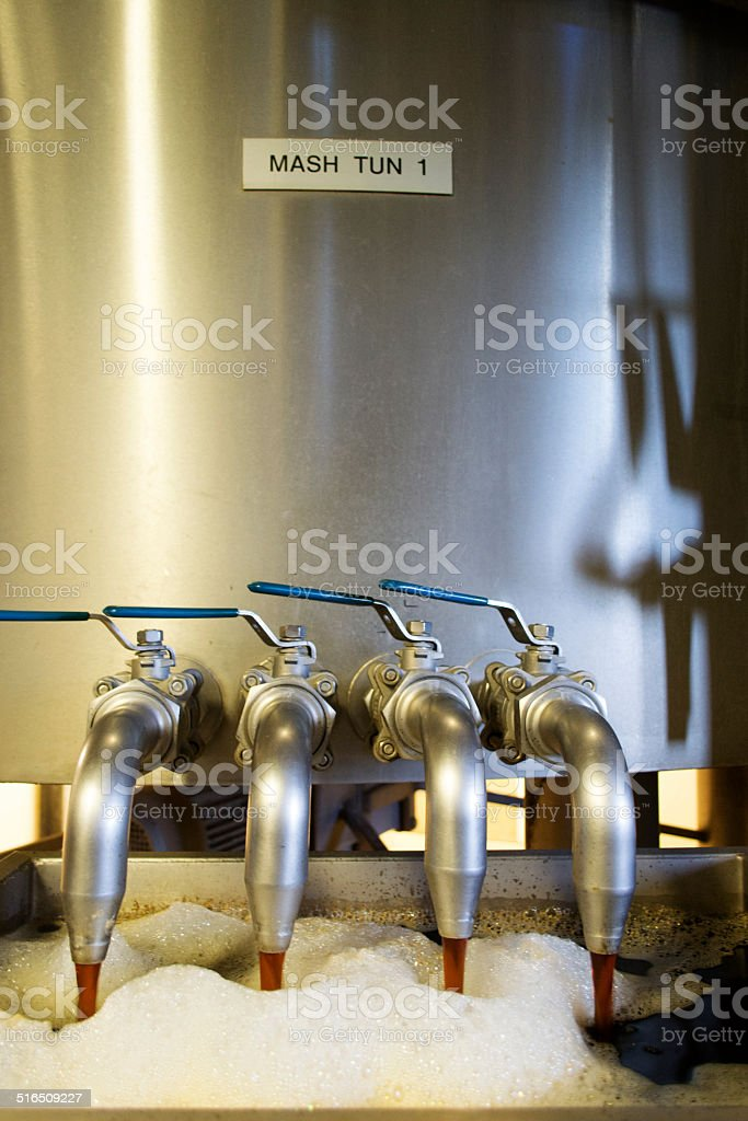 Beer flowing out of Mash-tun stock photo