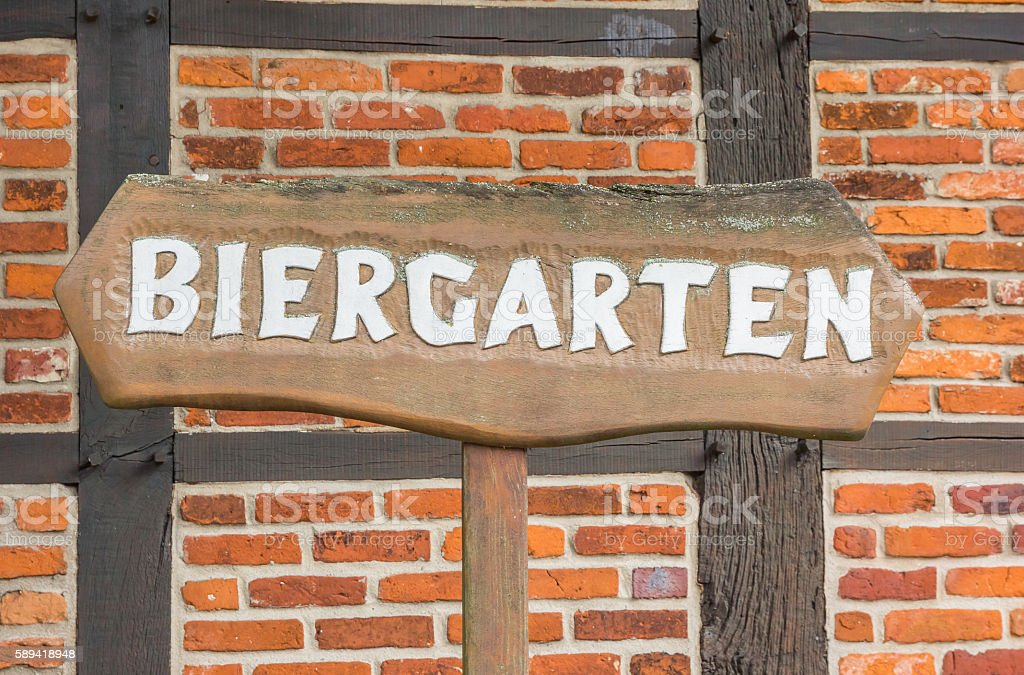 Beer garden sign in front of a half-timbered wall stock photo