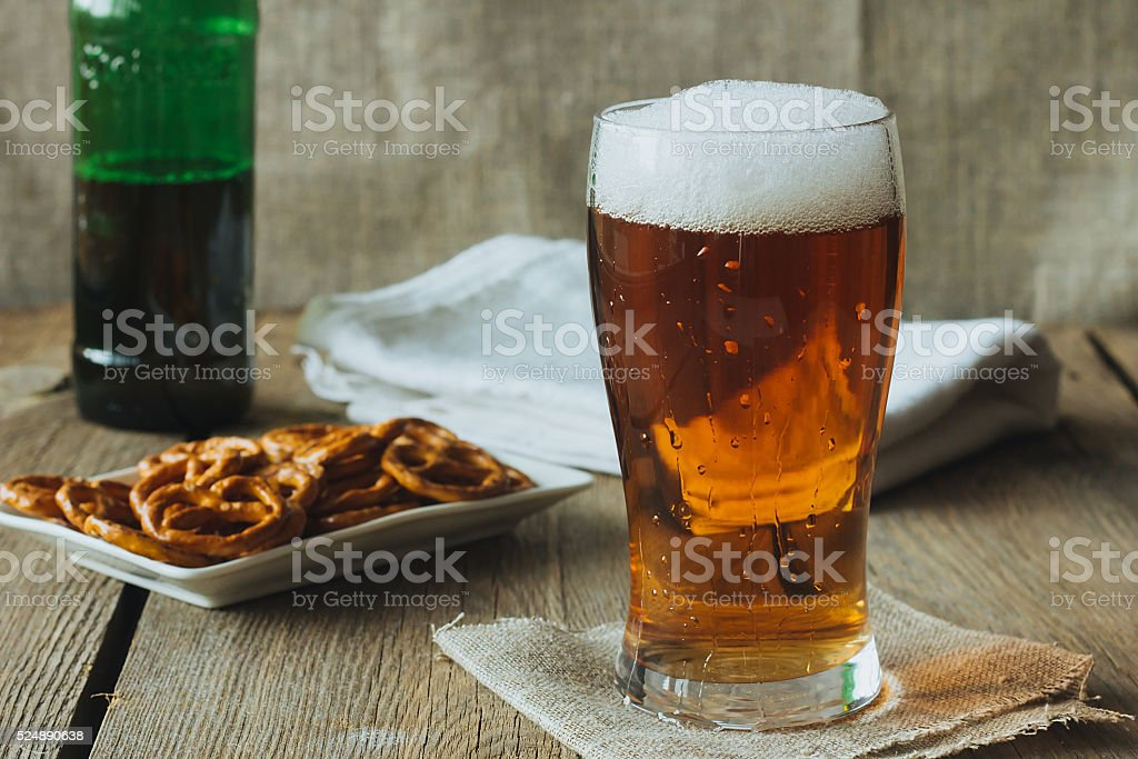Beer glass and snacks on wooden table stock photo