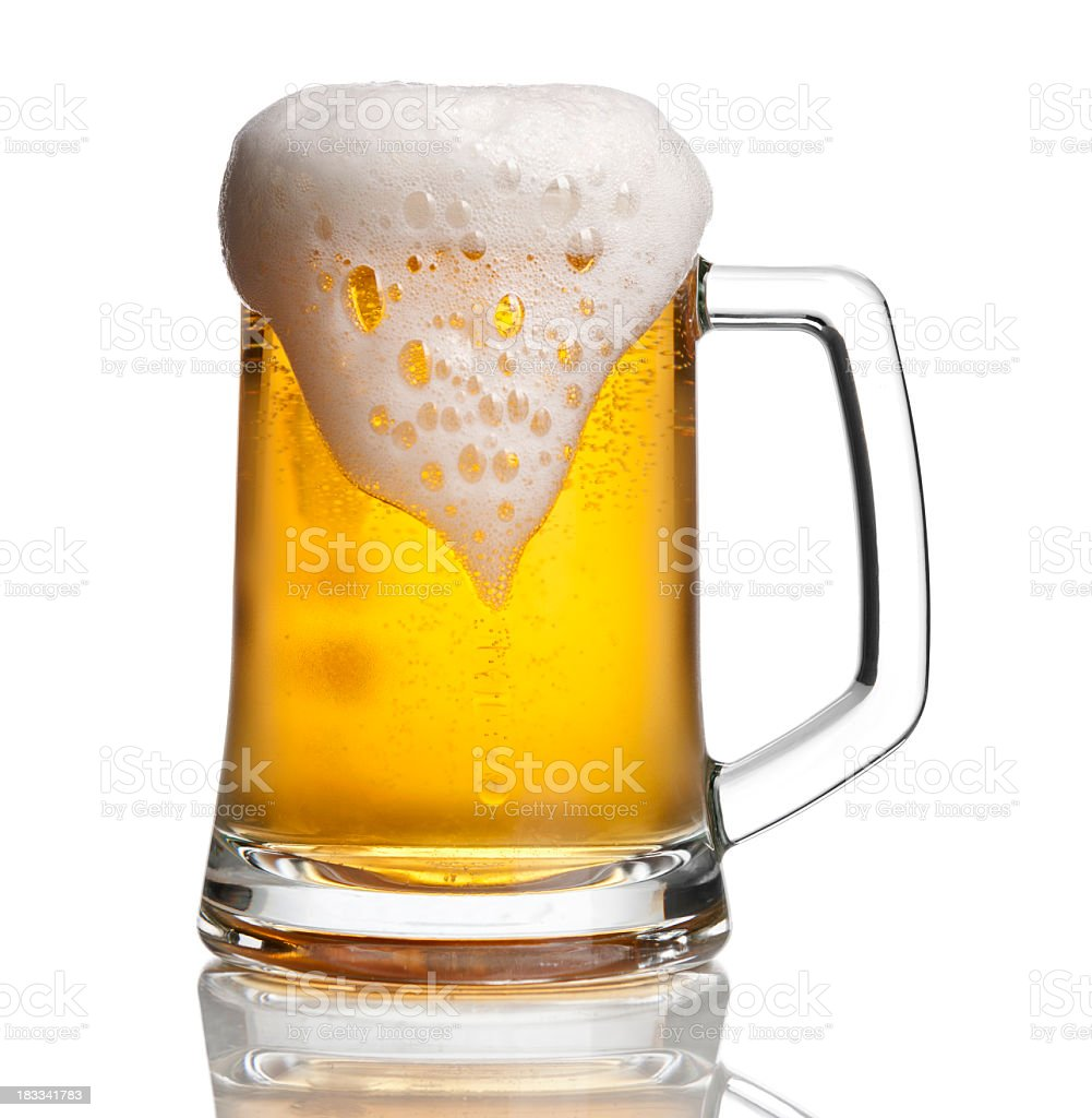 Beer glass with overflowing foam stock photo